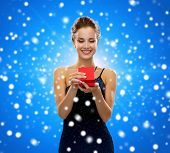 winter holidays, christmas, presents, luxury and people concept - smiling woman in dress holding red gift box over blue snowy background