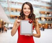 christmas, holidays, technology and people concept - smiling woman in red dress with tablet pc computer over shopping center background