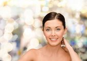 beauty, people and health concept - smiling young woman with bare shoulders over lights background