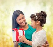 christmas, holidays, celebration, family and people concept - happy mother and child girl with gift box over yellow lights background