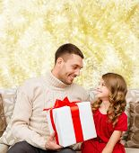 family, christmas, holidays and people concept -smiling father and daughter with gift box over yellow lights background