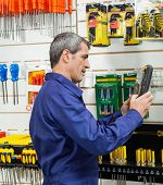 Side view of worker looking at packed product in hardware store