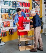Full length of young salesman assisting senior man in buying tools at hardware store