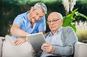 stock photo of retirement  - Male caretaker assisting senior man in using digital tablet at nursing home porch - JPG