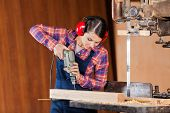 Young female carpenter using drill machine on wood at bandsaw in workshop