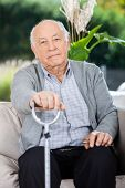 Portrait of elderly man holding metal walking stick while sitting on couch in nursing home porch