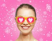 love, happiness, holidays, christmas and people concept - smiling teenage girl in sunglasses with hearts over pink background