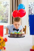 Boy blowing candles on birthday cake at home