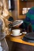 Midsection of young woman entering pin in card-reader at cafe