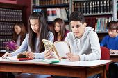 Male and female friends studying at table with classmates in library