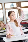 Cute little schoolgirl looking away while raising hand at desk in classroom
