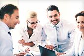 smiling businesswoman with team on meeting in office