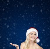 Young girl in Christmas cap gestures palm up, on blue snowy background