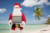 christmas, advertisement, technology, travel and people concept - man in costume of santa claus with laptop computer over tropical beach background