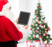 christmas, holidays, advertisement, technology and people concept - man in costume of santa claus with tablet pc computer showing blank screen over living room with tree background