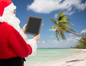 christmas holidays, advertisement, technology, travel and people concept - man in costume of santa claus with tablet pc computer showing blank screen over tropical beach background