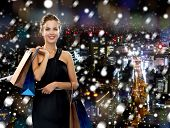shopping, sale, christmas, people and holidays concept - smiling woman in evening dress with shopping bags over snowy night city background