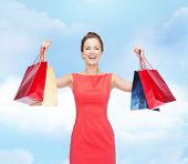 shopping, sale, christmas and holiday concept - laughing elegant woman in red dress with shopping bags