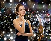 people, holidays, christmas and glamour concept - smiling woman in evening dress showing earrings over snowy night city background