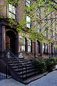 stock photo of brownstone  - A residential New York Philadelphia Boston or Chicago brownstone townhouse building with black fence and steps in front - JPG