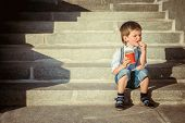 Little boy on the steps eating chips