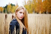 The Girl In A Leather Jacket Among A Yellow Grass
