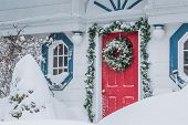 A red door decorated for Christmas in a snow storm.