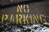 No parking sign on asphalt with snow.