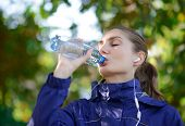 Young Beautiful Sports Woman Drinking Water During Exercises. Active Lifestyle