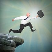Senior businessman jumping from a edge of cliff. Career and insurance metaphor.