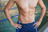 Close up mid section of a shirtless fit swimmer by the pool at leisure center
