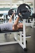 Side view of young muscular man lifting barbell in the gym