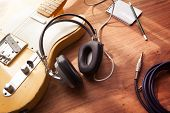 Постер, плакат: Guitar recording scene An electric guitar memo pad and a professional grade headphones on a rust