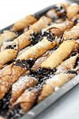 stock photo of confectioners  - Tray full of freshly filled cannolis with chocolate chips and confectioners sugar - JPG