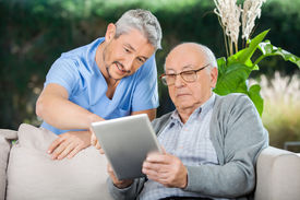 foto of nursing  - Male caretaker assisting senior man in using digital tablet at nursing home porch - JPG