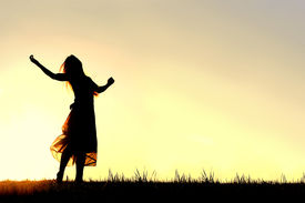 foto of godly  - A woman wearing a long skirt with long blonde hair is dancing and praising God while silhouetted against the evening sky - JPG