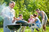 foto of bbq party  - Family having a barbecue party in their garden in summer - JPG