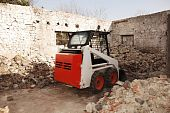 stock photo of skid-steer  - A bobcat skid steer loader in a partially demolished derelict old Italian farm building - JPG