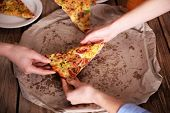 stock photo of take out pizza  - Friends hands taking slice of pizza - JPG