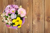 stock photo of bouquet  - Colorful flowers bouquet on wooden table - JPG