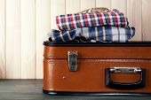 picture of old suitcase  - Vintage suitcase with clothes on wooden background - JPG