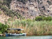 stock photo of dalyan  - Pleasure boat with tourists in the mouth of the Dalyan River under Lycian tombs