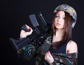 foto of assault-rifle  - Portrait of a woman in a military uniform with an assault rifle over black background - JPG
