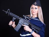 pic of assault-rifle  - Beautiful young woman in a marine uniform with an assault rifle over black background - JPG