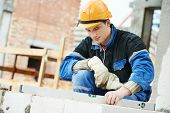 stock photo of mason  - construction mason worker bricklayer working level levelling bricks - JPG