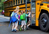 stock photo of youngster  - A group of young children getting on the schoolbus - JPG