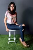 image of denim wear  - fashion shoot of beautiful woman sitting on white chair wearing crop tees denim trousers and gold wedges - JPG