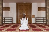stock photo of god  - African Muslim Man Making Traditional Prayer To God While Wearing A Traditional Cap Dishdasha - JPG