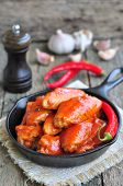 stock photo of saucepan  - Hot Chicken Wings Barbecue in Black Saucepan isolated - JPG