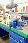 image of workbench  - The image of a old vice on a metal workbench - JPG